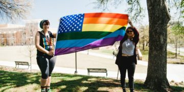 Two women holding up a flag that represents the LGBT community.