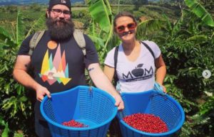 Two people holding fruits in large blue bins in a field.