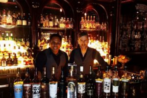 Two bartenders standing behind the bar.