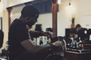 A man giving a haircut to a customer.