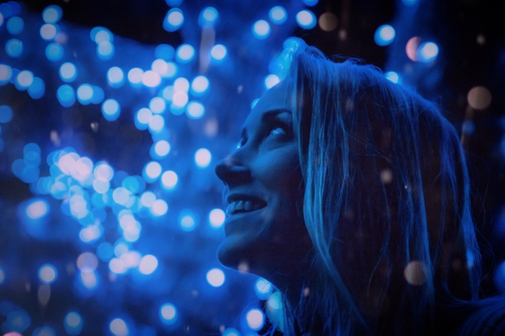 A woman looking up at blue lights