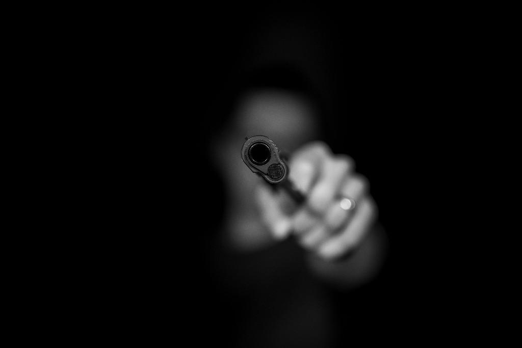 A person holding a gun in their hand in the dark