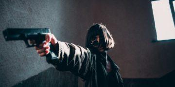 A woman pointing a black hand gun