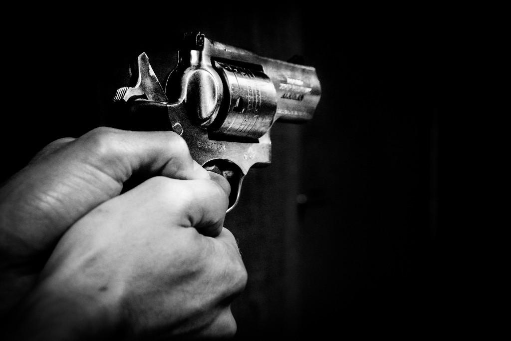 A person's hands holding a black gun
