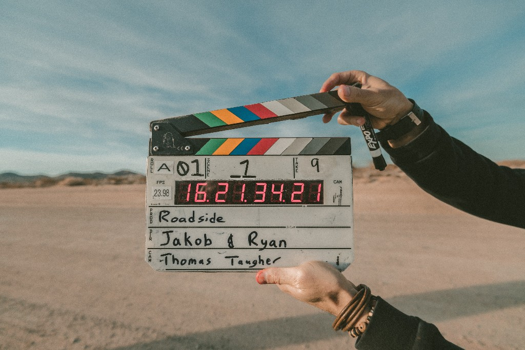 A pair of hands holding a clapperboard.