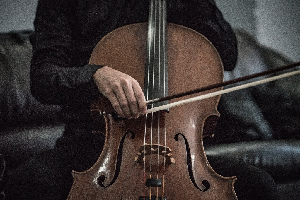 A person in a black shirt playing the cello.