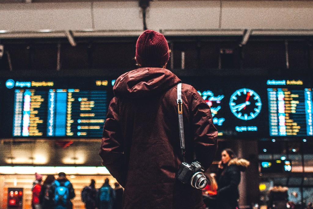 A person looking at screens at an airport.