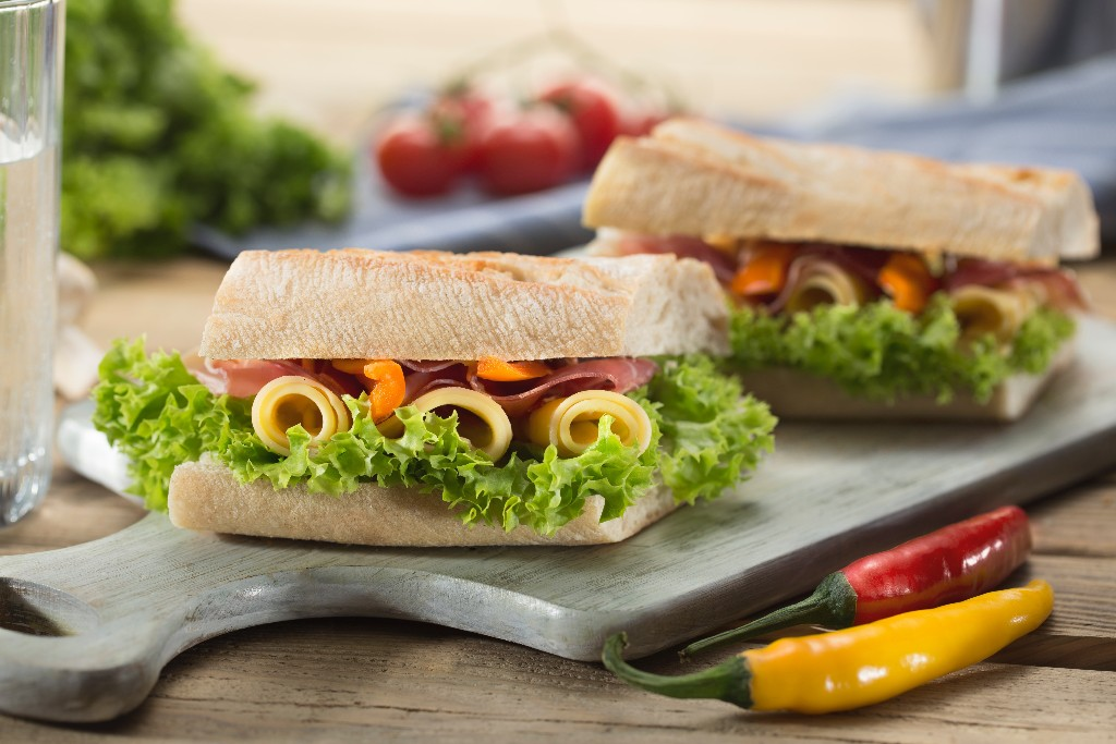 Two sandwiches on a wooden cutting board.