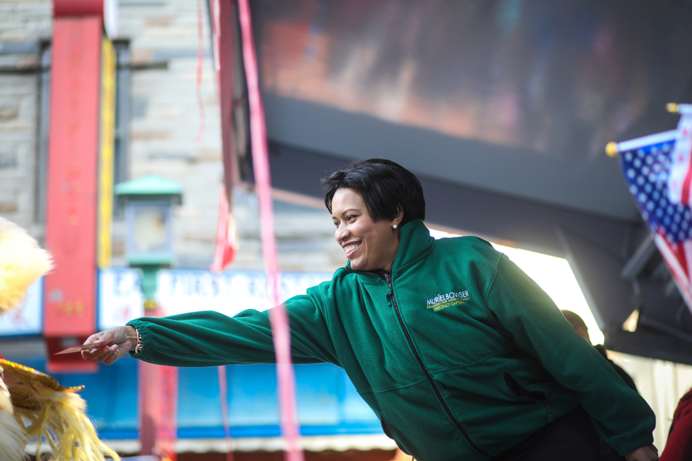 DC Mayor Muriel Bowser feeds a dancing dragon a note at the Chinese New Year Parade in Chinatown, February 18, 2018.