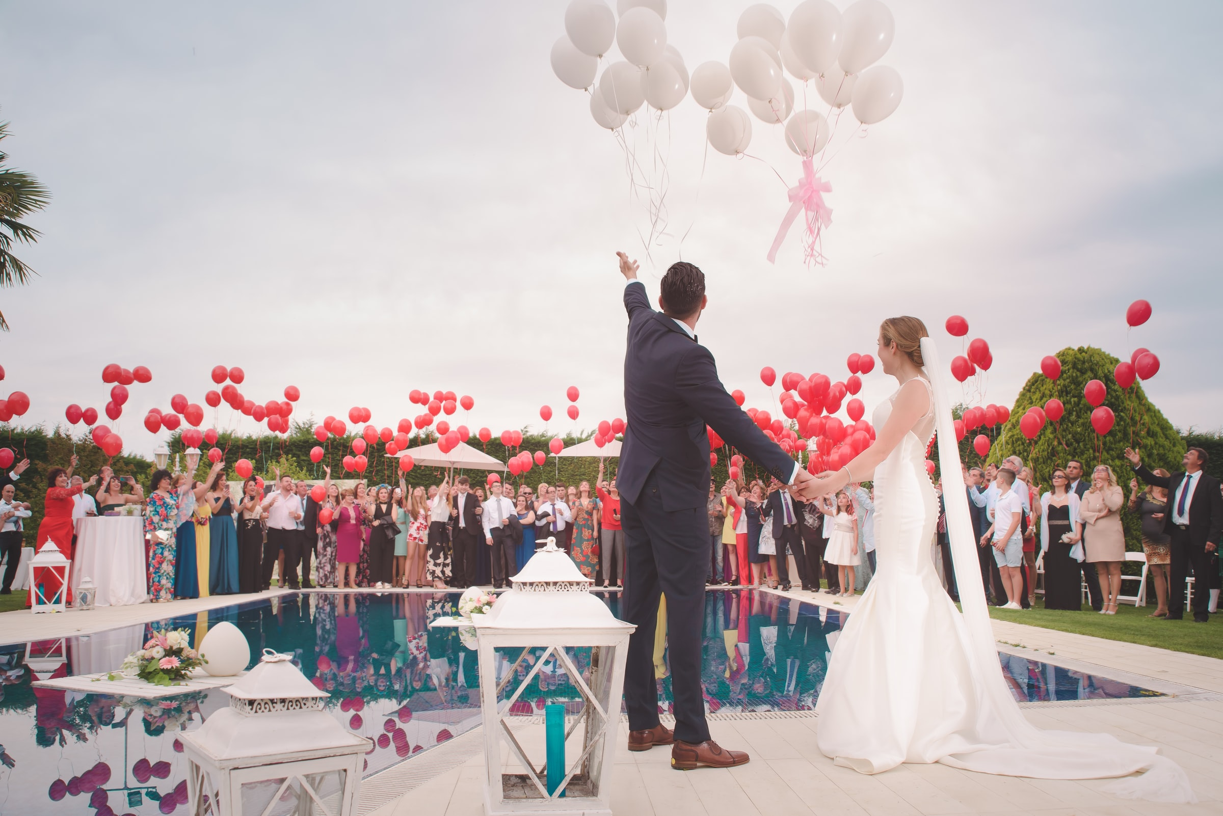 A bride and groom look at balloons being flown