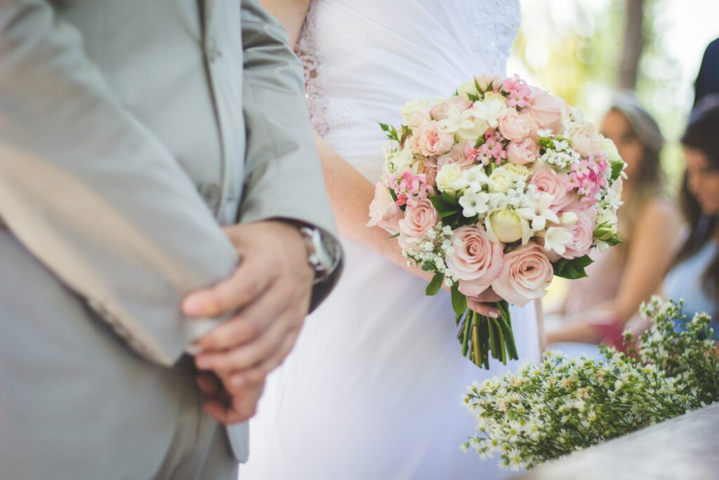 A bride holding flowers stands against the groom